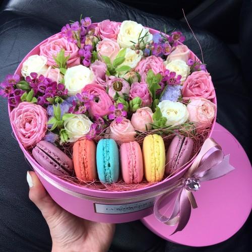 Kastīte ar roza krāsa rozēm un macarons cepumien