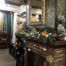 Garland of alive christmas tree and new year decoration on a fireplace