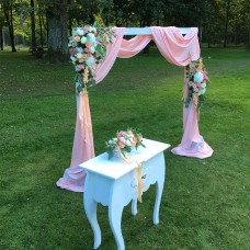 Archway for wedding ceremony with flowers and peach colored fabric