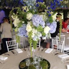 Augsta ziedu kompozicija ar hortenzijām un delfīnijām viesu galdā